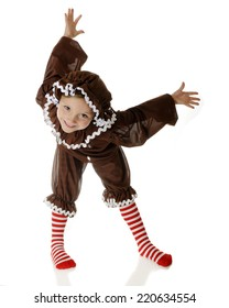 "An adorable ""gingerbread girl"" happily dancing, with her body in contortions.  On a white background."
