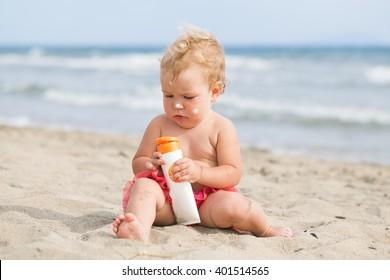 Adorable girl at beach applying sunblock cream, portrair