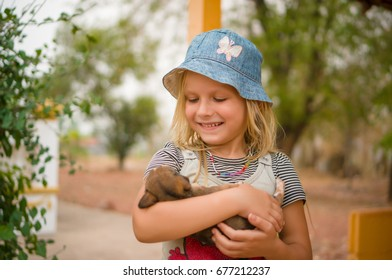 Adorable girl in blue hat play with puppy on hands