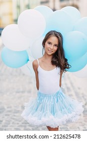 Adorable girl with blue and white balloons