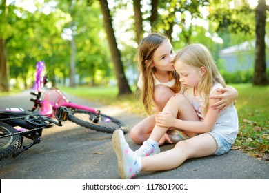 Adorable girl comforting her little sister after she fell off her bike at summer park. Child getting hurt while riding a bicycle. Active family leisure with kids.