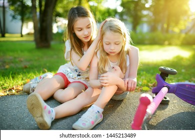 Adorable girl comforting her little sister after she fell off her scooter at summer park. Child getting hurt while riding a kick scooter. Active family leisure with kids.