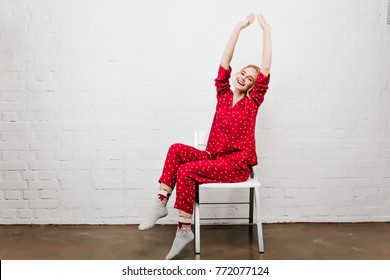 Adorable girl in cute sleepwear and socks sitting on chair and laughing. Indoor portrait of positive young woman in red pajamas stretching with smile.