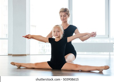 Adorable girl dancer and her teacher doing stretching in the ballet studio