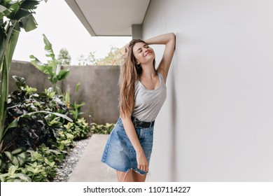Adorable girl in denim skirt relaxing during photoshoot near plants. Outdoor portrait of european woman smiling in morning while standing beside white wall.