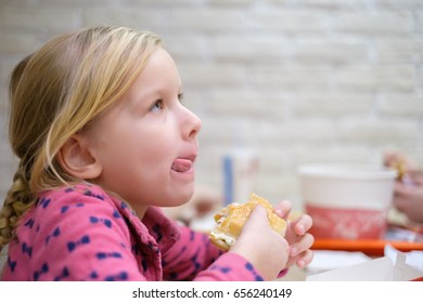 Adorable girl eat classic burger in fast food restaurant