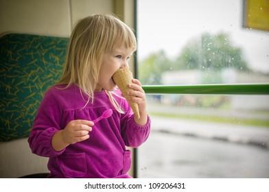 Adorable girl eat ice cream riding bus