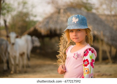 Adorable girl is exploring farm with cows on back