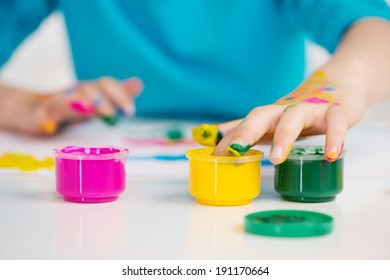 Adorable girl finger painting. Adorable girl finger painting - just dipping her finger into the paint