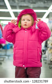 Adorable girl fitting winter jacket and hat in sport store