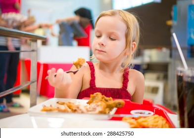 Adorable girl have meal with chicken,  soda drink and fried potatoes at fast food restaurant