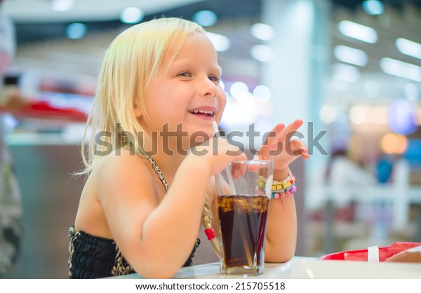 Adorable girl have meal with soda drink and fried potatoes at fast food restaurant