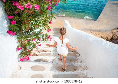Adorable girl having fun outdoors runs on the stairs near the sea on the island of Mykonos
