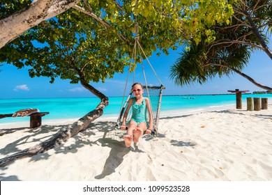 Adorable girl having fun swinging at tropical island beach