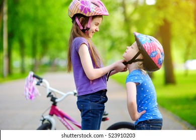 Adorable girl helping her little sister to put a bicycle helmet on