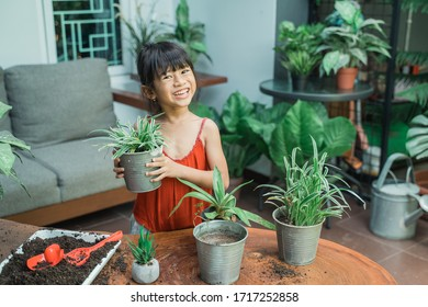 adorable girl holding flower pot while gardening at home