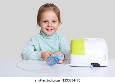 Adorable girl inhales couple containing medication, wants to stop chest coughing, uses inhalor, has medical procedure, asthmatic attack isolated over white background. Home treatment concept.