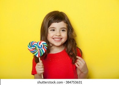 Adorable girl licking lollipop, on yellow background