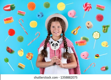 Adorable girl with lollypop and flying candies on color background