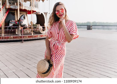 Adorable girl in long striped dress enjoying festive in amusement park. Outdoor photo of blissful female model with blonde hair holding straw hat.