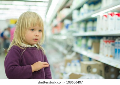 Adorable girl in milk department in supermarket
