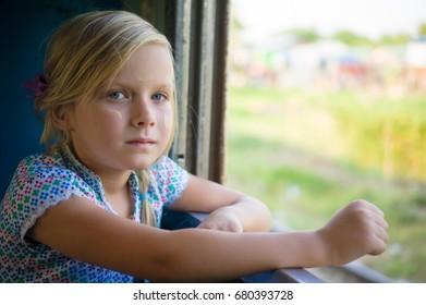 Adorable girl near window in train