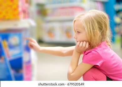 Adorable girl in pink explore toys in kids supermarket