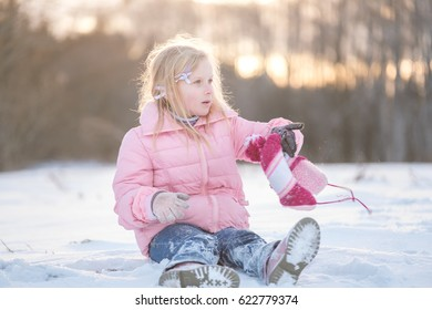 Adorable girl in pink jacket in snow winter park on sunset