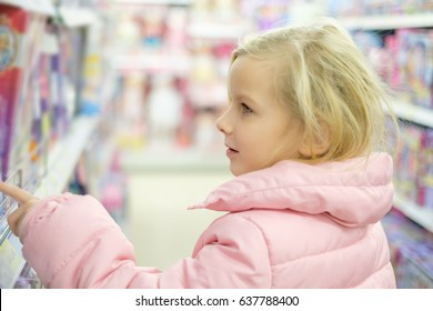 Adorable girl in pink jacket and white winter hat select toys in kids store