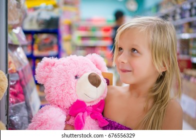 Adorable girl with pink plush teddy bear in shop