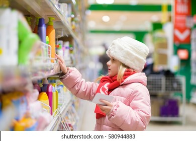 Adorable girl in pink winter jacket and white fur hat selects cosmetics on shelf in supermarket