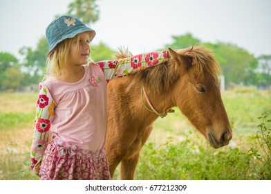 Adorable girl playing with baby horse on farm