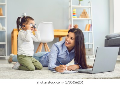 Adorable girl playing with glasses while her mom doing online freelance job at home. Working from home and parenting