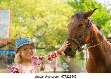 Adorable girl is playing with horse on farm