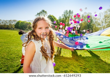 Adorable girl playing parachute with her friends