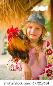 Adorable girl playing with tiny rooster on hands