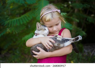 Adorable girl in red dress hold nice cat on hands