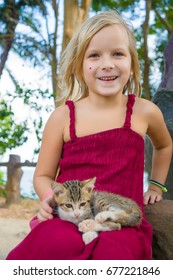 Adorable girl in red dress plays with little kitten sitting on the bench