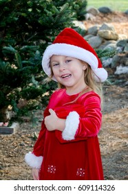 An adorable girl in red santa hat and red dress, holds a red wrapped gift box