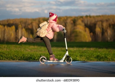 Adorable girl ride on kick scooter in park with blurry background