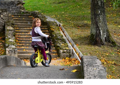 Adorable girl riding a bike on beautiful autumn day in the old park. Cesis, Latvia