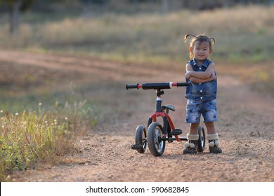 Adorable girl riding a bike on beautiful autumn day