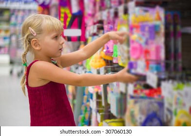 Adorable girl selects blue toy dolls on shelves in supermarket