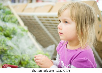 Adorable girl at shopping cart select fruits in supermarket