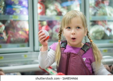 Adorable girl sit on shopping cart in front of fridges
