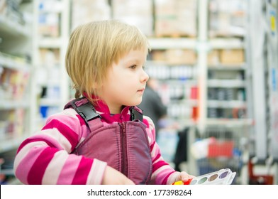 Adorable girl sit on shopping cart  in supermarket