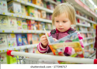 Adorable girl sit on shopping cart with kids book in supermarket