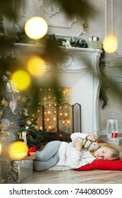 Adorable girl sleeping on the floor on red pillow by fireplace and decorated Christmas tree