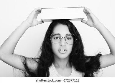 Adorable girl studying with eyeglasses and book on the head on white background