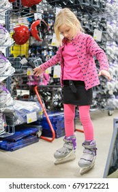 Adorable girl tries ice skate boots in outdoor sports store